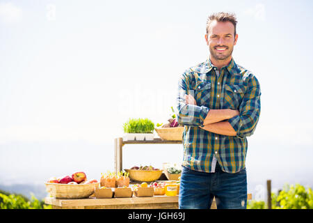 Portrait of smiling young man with arms crossed standing at farm Banque D'Images