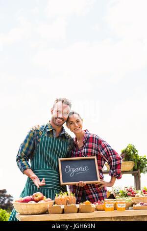 Portrait of young couple avec tableau noir la vente de légumes biologiques contre ciel à farm Banque D'Images