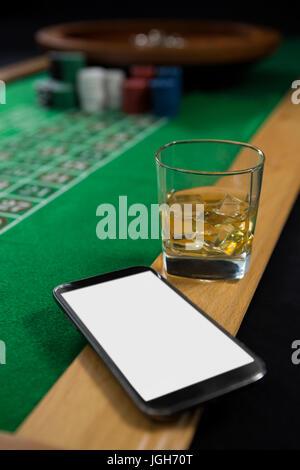 Close-up of mobile phone et verre de whisky sur la table de la roulette au casino Banque D'Images