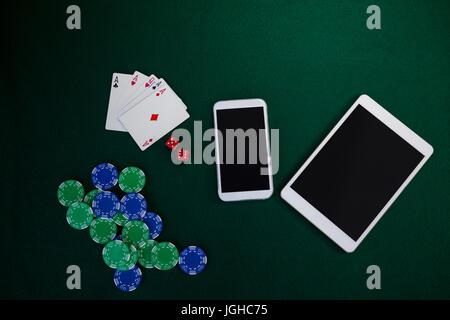 Gadgets électroniques, des cartes à jouer, d'un téléphone mobile, dés et jetons de casino sur table de poker dans le casino