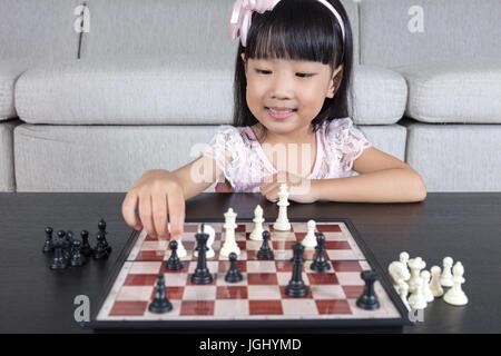 Chinois asiatique petite fille jouant aux échecs échecs dans la salle de séjour à la maison