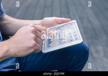 Personne à l'aide d'occasionnels ordinateur tablette numérique pour analyser un tableau de bord financier avec des Banque D'Images