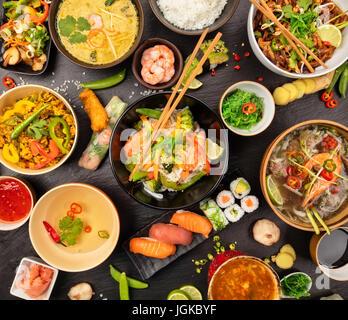 Tableau des aliments asiatiques avec différents types de plats chinois, nouilles, poulet, porc, boeuf, riz, soupe aigre, rouleaux de printemps, sushis, les crevettes et bien d'autres. Servi