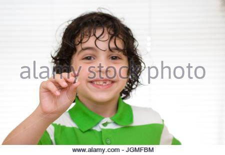 Stade de développement humain: enfant tenant une dent de lait qui vient de tombé sur fond blanc Banque D'Images