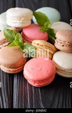 Macarons multicolores et de menthe fraîche gros plan sur une table. La verticale Banque D'Images