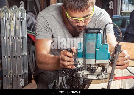 Une jeune brunette homme portant des lunettes et un t-shirt gris carpenter builder pre-works les bords de la planche Banque D'Images