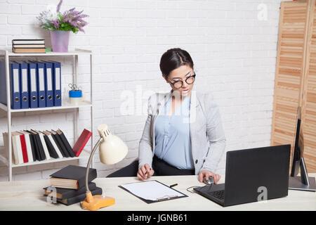 Fille d'affaires est assis à un ordinateur dans le document du Bureau des dossiers Banque D'Images