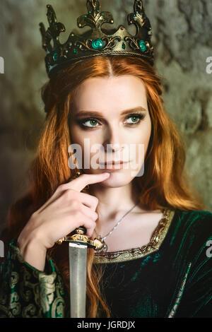 Portrait d'une belle femme aux cheveux rouge en vert robe médiévale Banque D'Images