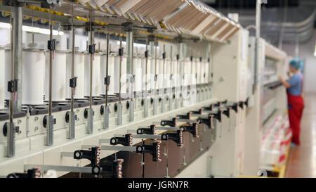 Rangée de machines automatisées pour la fabrication de fils. Yarn thread s'exécutant dans la machine. Banque D'Images