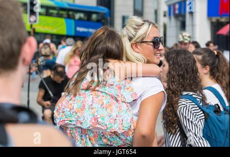 Jeune mère portant sa fille sur son dos au travers des foules dans une ville surpeuplée. Banque D'Images