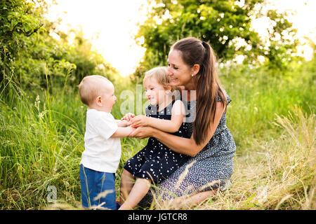 Jeune mère avec peu d'enfants dans la nature d'été ensoleillé Banque D'Images