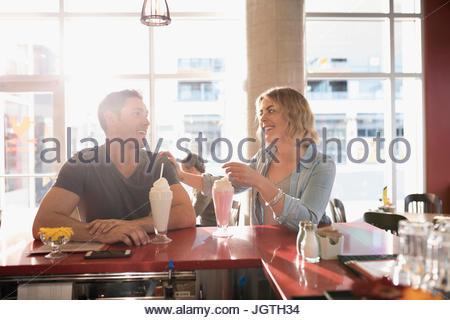 Jeune couple de parler, de boire des milkshakes à diner counter Banque D'Images