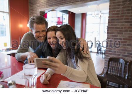 Les parents et fille adolescente en tenant au comptoir diner selfies Banque D'Images