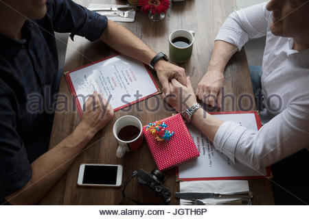 Homme affectueux gay couple holding hands, celebrating birthday at diner booth Banque D'Images
