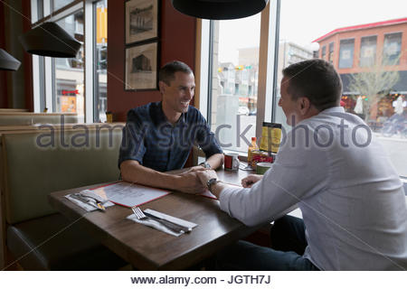 Homme affectueux gay couple holding hands at diner booth Banque D'Images