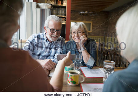 Senior friends using cell phone in diner booth Banque D'Images