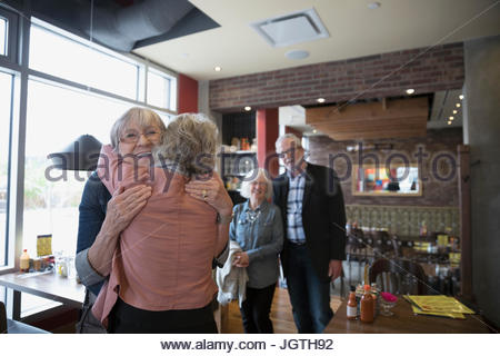 Senior friends accueil, hugging in diner Banque D'Images