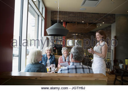 Waitress de senior friends dining in diner booth Banque D'Images