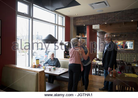 Senior friends accueil, hugging at diner booth Banque D'Images