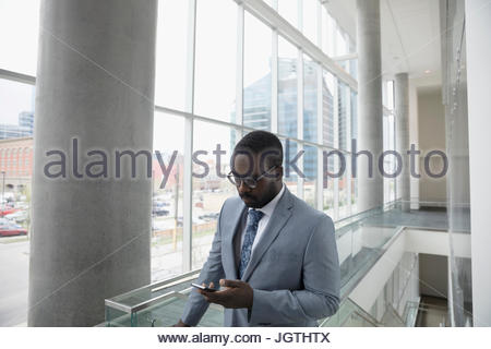 Businessman texting with cell phone in office Banque D'Images