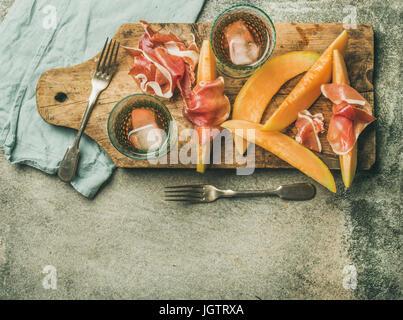 Vin d'été partie. Flatlay de vin snack-jambon prosciutto, melon et verres de vin rose avec de la glace sur planche Banque D'Images
