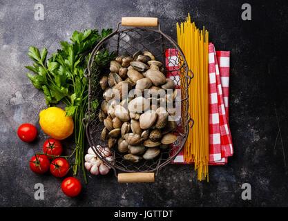 Les aliments crus Ingrédients pour la cuisson des spaghettis alle vongole sur fond sombre Banque D'Images