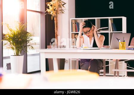 Fatigué de l'Asie et du milieu de travail dans un bureau moderne Banque D'Images