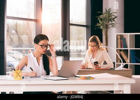 Les jeunes femmes d'multiethnique en soirée travaillant au bureau moderne Banque D'Images