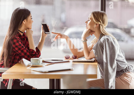 Vue latérale des jeunes femmes à parler tout en ayant déjeuner d'affaires dans la région de cafe Banque D'Images