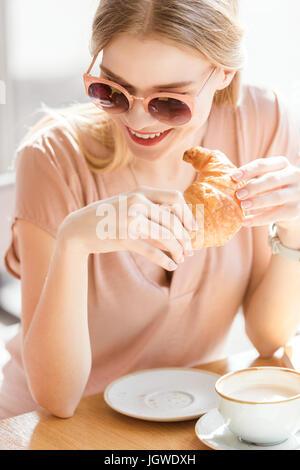 Young woman eating croissant tout en restant assis dans un café, une pause café Banque D'Images