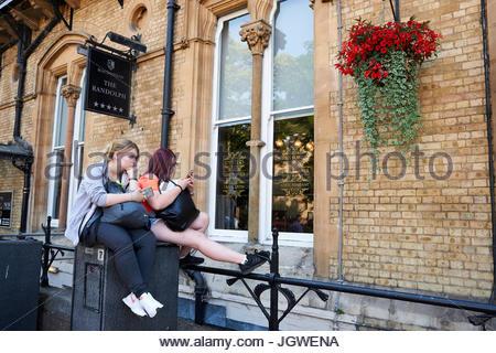 Deux adolescentes assis sur le mur à la recherche de téléphones mobiles à l'extérieur de l'hôtel Randolph dans l'Oxfordshire Banque D'Images