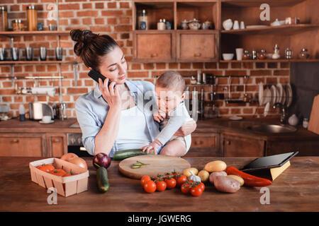 Portrait de Mère avec fils en conversation sur smartphone et à préparer le dîner dans la cuisine Banque D'Images
