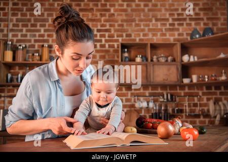 Maman avec son bébé lecture livre avant de préparer le dîner dans la cuisine Banque D'Images