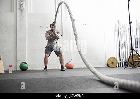 Homme travaillant sur la bataille avec la corde dans l'entraînement en salle de sport Banque D'Images
