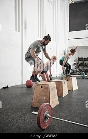 Les amis sauter sur boîte de conditionnement physique dans l'entraînement en salle de sport Banque D'Images