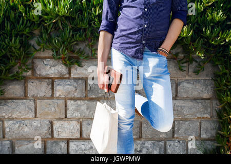 Man holding shopping bags par brick wall Banque D'Images