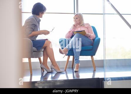 Les femmes d'affaires ayant discussion en séance Banque D'Images