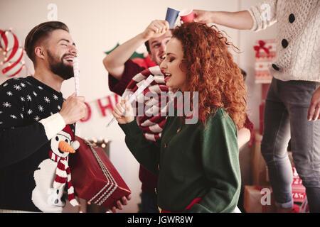 Jeune homme et femme chantant avec microphones prétendre at Christmas party