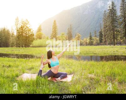 Woman practicing yoga pose par lake in Yosemite National Park, California, USA Banque D'Images