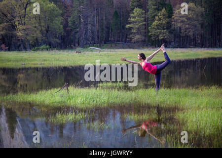 Woman practicing yoga posture de l'arbre by lake in Yosemite National Park, California, USA Banque D'Images