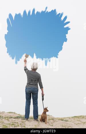 Senior woman with dog on laisse la peinture ciel bleu dans l'air Banque D'Images
