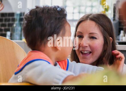 Mère regardant bébé garçon en chaise haute smiling Banque D'Images