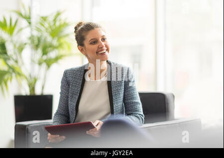 Happy young businesswoman using digital tablet in office