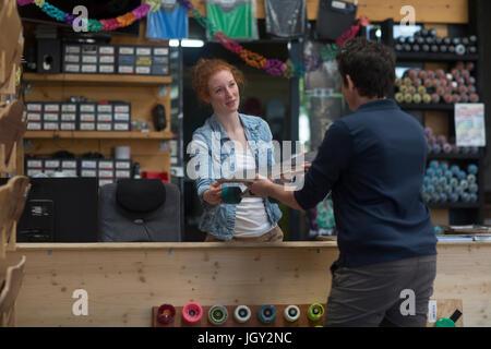 Femme travaillant dans skateboard shop, remise au client de planche à roulettes Banque D'Images