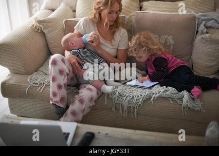 Nourrir bébé mère fils et fille aider with digital tablet
