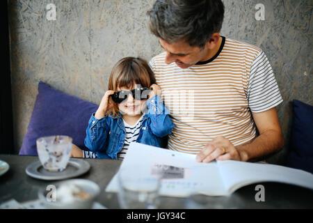 Fille jouant avec les lunettes de père en cafe Banque D'Images