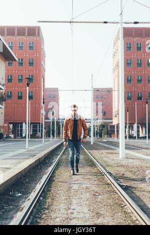 Cool jeune homme barbu à marcher le long des lignes de tramway de la ville Banque D'Images