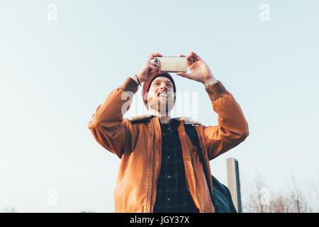 Heureux jeune homme hipster en tenant selfies smartphone contre le ciel bleu Banque D'Images