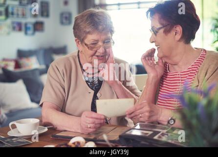Deux femmes âgées bavarder tout en regardant de vieilles photos à table Banque D'Images