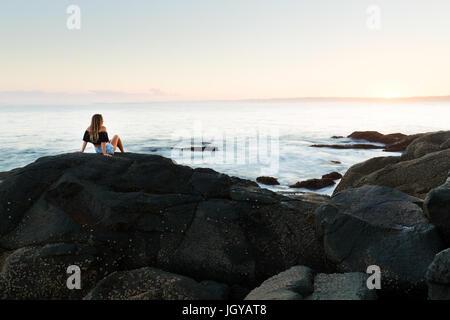 La santé de la jeune fille est assise sur un rocher et regarde le coucher du soleil sur un paysage magnifique en Banque D'Images